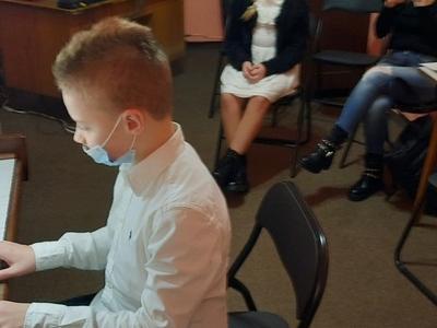 chłopiec w białej koszuli w maseczce grający na fortepianie