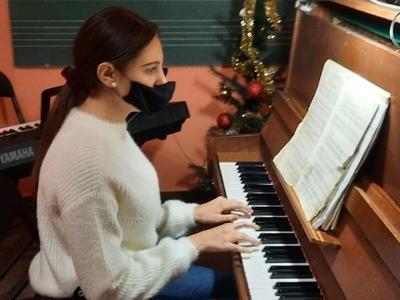 kobieta w białym sweterku gra na fortepianie