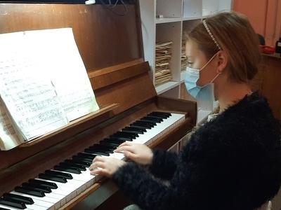 dziewczynka grająca na fortepianie w maseczce